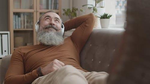Mann mit Kopfhörern auf Sofa