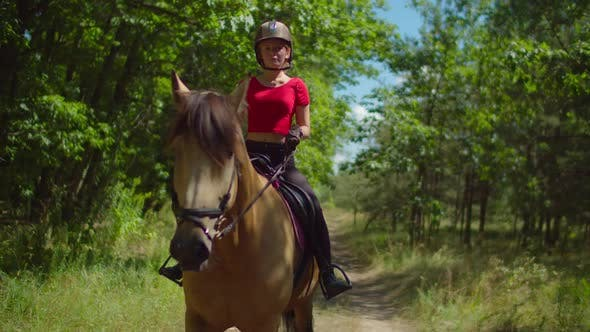 Teenage Girl Jockey Riding Horseback in Nature