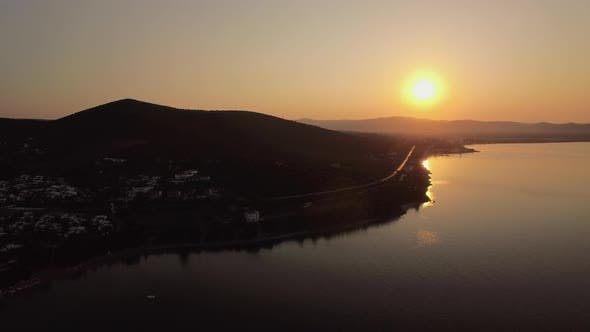 Thumbnail for Flying Over Trikorfo Beach with Cottages and Green Uplands at Sunset, Greece