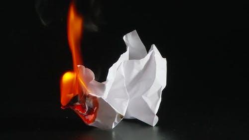 ball of white paper beginning to burn