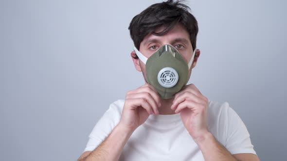 Thumbnail for Man Puts a Respiratory Mask on Her Face on a Gray Background