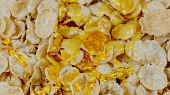 Thumbnail for Honey Flows on Corn Flakes Cereal Breakfast Close Up. Natural Immunity Products
