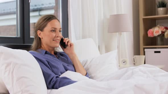 Thumbnail for Happy Woman Calling on Smartphone in Bed at Home