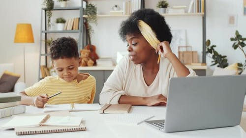 Afro-American Female Tutor Giving Lesson to Little Boy at Home