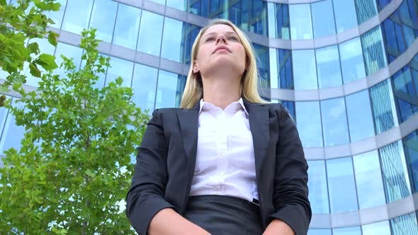 Thumbnail for A Young Beautiful Businesswoman Stands in Front of an Office Building and Looks Around Proudly