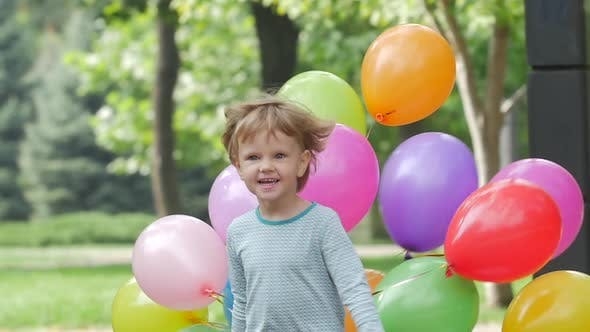 Emotional Girl Runs with Multicolored Balloons