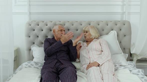 Thumbnail for Senior Elderly Couple in Pyjamas Lying on Bed Having an Argument in Bedroom. Grandparents Quarrel