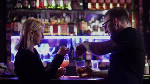 Thumbnail for A Beautiful Couple Drink Cocktails at the Bar Counter. Man in Glasses and Blond Woman Talking