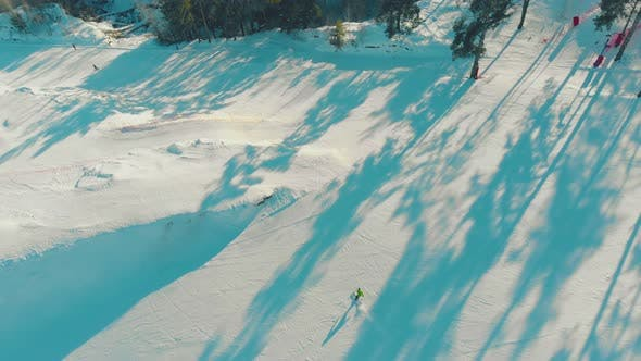 People Ski and Snowboard Along White Slope Aerial View