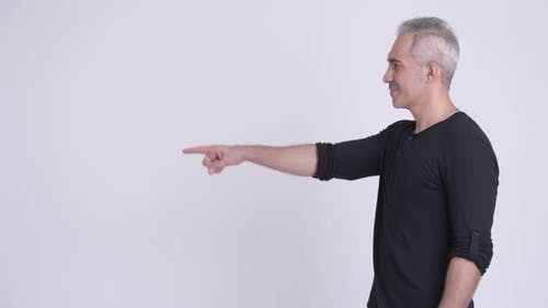 Profile View of Happy Persian Man Pointing Finger Against White Background