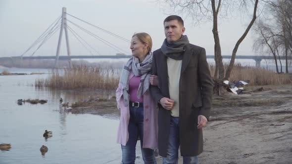 Thumbnail for Happy Loving Caucasian Couple with Age Difference Walking Along Riverbank in City Park. Portrait of