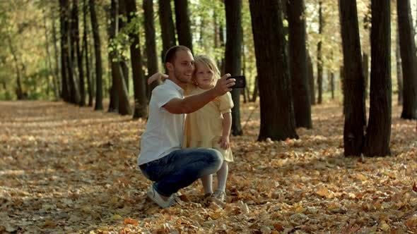 Thumbnail for Glückliche Familie mit Selfie mit Smartphone im Herbstpark