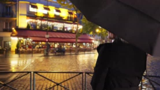Thumbnail for Happy free spirited senior woman dancing in the rain on rainy Paris night