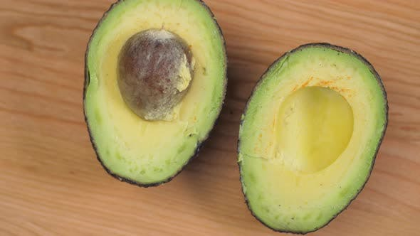 Thumbnail for Avocado Halves With Nut Spinnin On Cutting Board 01