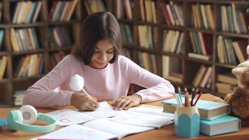Happy Indian Latin Kid School Girl Pupil Studying at Home Sitting at Desk