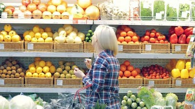 Woman Picking Vegetables in a Supermarket