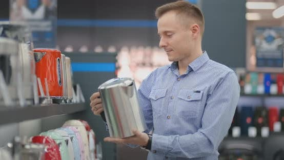 Cover Image for Young Man Chooses Electric Kettle for His New Home in Appliances Store