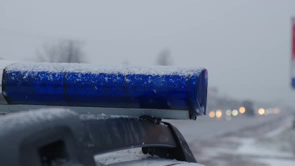 Blue Lights of a Police Car Flash Against the Snow in the Evening