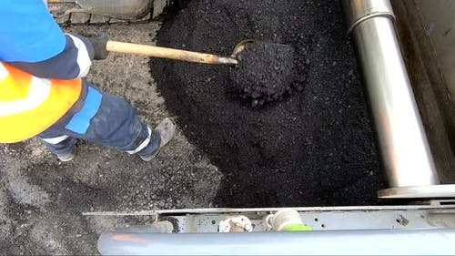 Worker Is Laying Asphalt. Road Works on a Construction Site. The Distribution of the Asphalt with a
