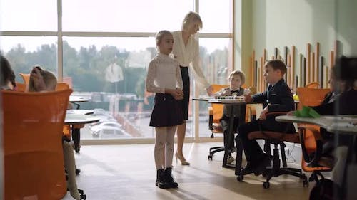 Wide Shot of Schoolgirl Declaiming in Classroom with Teacher and Classmates Listening