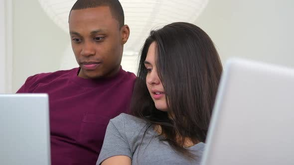 Thumbnail for African American and Caucasian couple using laptop computers on couch