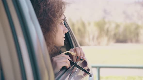Thumbnail for Curly Woman Holds Sunglasses and Looks Out of Auto Window