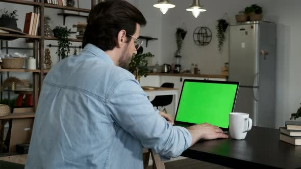 Over the shoulder shot of man working online on laptop with green screen display in living space