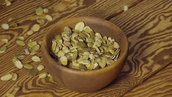SLOW: Peeled Pumpkin Seeds Fall Into A Wooden Dish On A Table