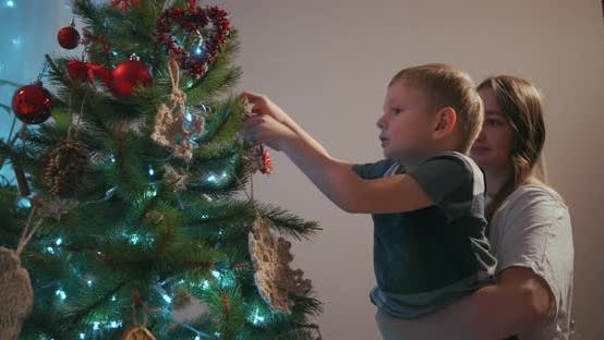 Thumbnail for A Mother Picks Up Her Son To Decorate a Christmas Tree