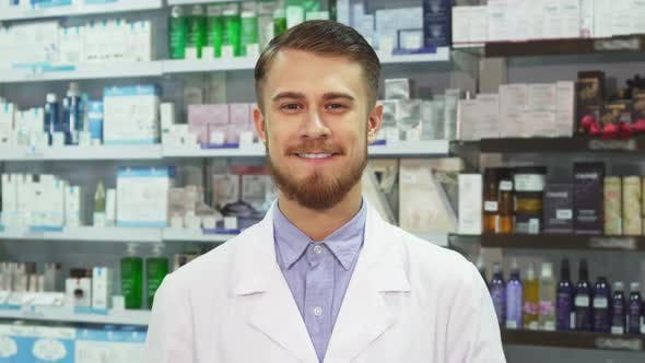 Young Pharmacist Showing Medication and Smiling