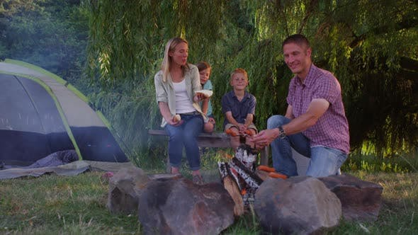 Thumbnail for Family roasting hot dogs at camp site