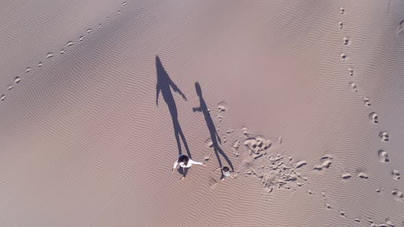 Aerial View of Mum and Son Walking Along Dunes