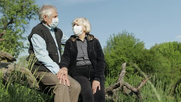 Senior Couple in Medical Masks During COVID-19 Coronavirus Quarantine in Park