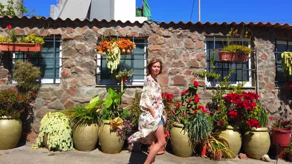 Thumbnail for Pretty Female Model in Walking with a Facade of Flowers in Background