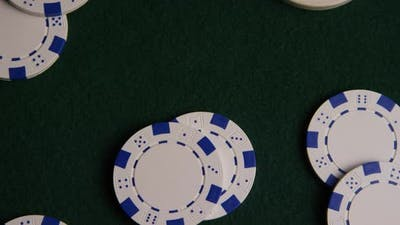 Rotating shot of poker cards and poker chips on a green felt surface - POKER 018