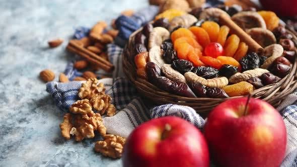 Thumbnail for Zusammensetzung von getrockneten Früchten und Nüssen in kleinen Weidenschale auf Steintisch platziert
