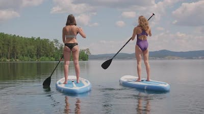 Women Practicing Stand Up Paddle Surfing