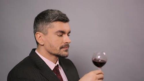 Experienced Winemaker Enjoying Tasty Red Wine at Cafe, Ripe Alcoholic Beverage