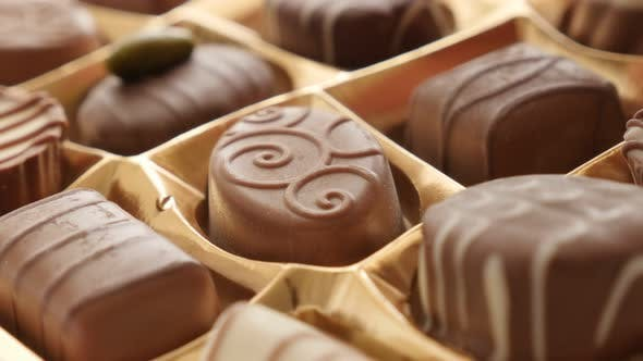 Chocolate from box picking by hand of  many different 4K 2160p 30fps UltraHD footage - Woman chosing