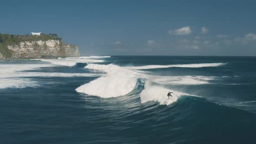 Surfer Rides the Big Waves at Blue Point Beach, Indian Ocean in Uluwatu, Bali, Indonesia, Aerial