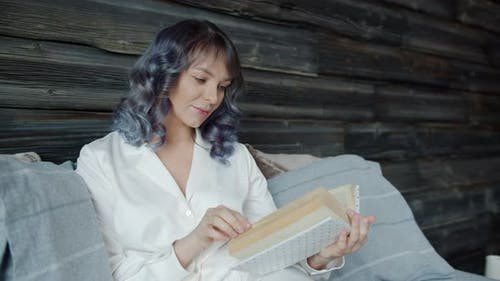 Slow Motion of Beautiful Young Lady Wearing Pajamas Reading Book in Bed