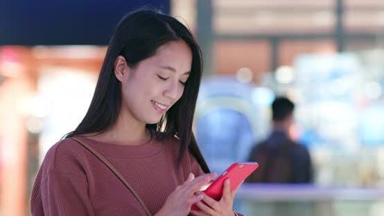 Cover Image for Woman use of mobile phone inside shopping center