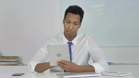Thumbnail for Afro-American Businessman Browsing Internet on Tablet