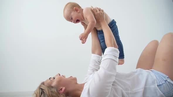 Alleinerziehende, Mutterschaft und Babyhood-Konzept - Mutter hält süßes Mädchen auf weißem Hintergrund