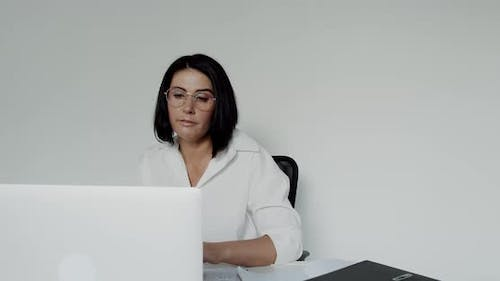 Female Lecturer in Glasses Chatting on a Laptop During Remote Learning in Office