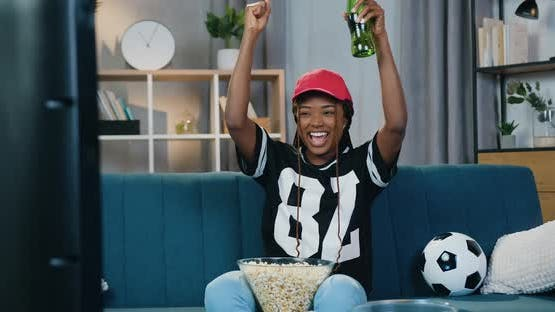 Dark-Skinned Female Fan which Celebrating Victory of Favourite Team with Raised hands