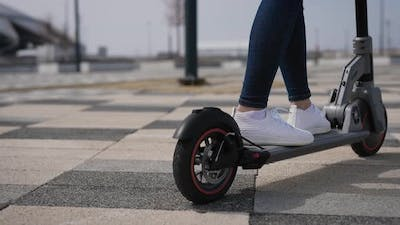 Women's Legs on an Electric Scooter