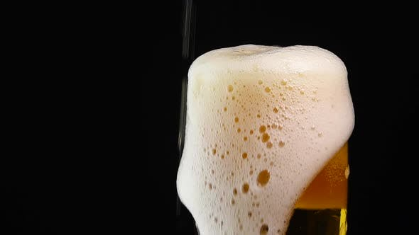Thumbnail for Close up pouring lager beer in glass over black