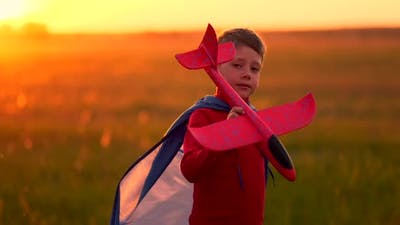 A Child at Sunset Fantasizes and Imagines Himself a Pilot at Sunset