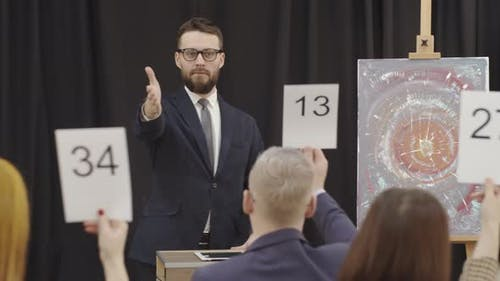 Male Auctioneer Selling Contemporary Artwork at Auction